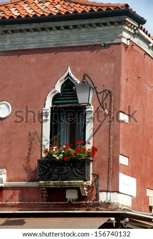 flowery balcony in Venetian style with arched windows of a residence in Venice - stock photo