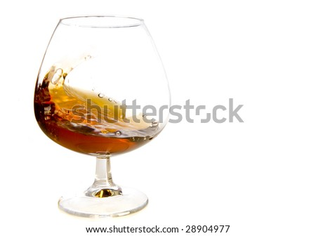 flowing cognac in glass on white ground - stock photo