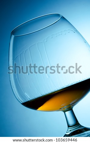 Flowing down drops of cognac in wineglass - stock photo