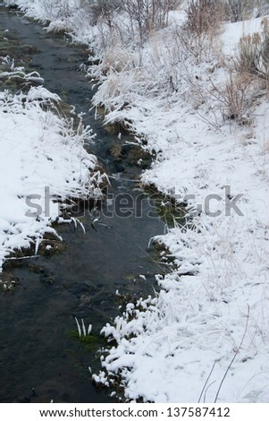 Flowing river with icy, snow banks - stock photo