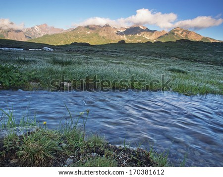 Flowing water and sunny mountain range
