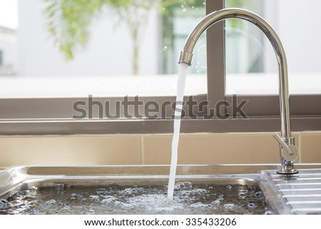 Flowing water into sink. (Cool colour filtered) - stock photo
