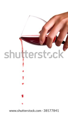 Flowing wine from a wineglass holding in woman's hand. Isolated on white background. - stock photo