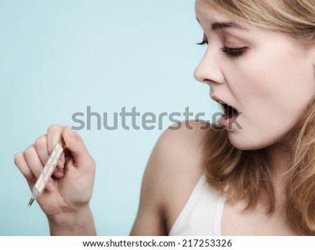 Flu cold grippe. Woman having high temperature. Sick girl with fever checking mercury thermometer on blue. - stock photo
