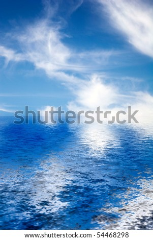 Fluffy cotton like clouds spread across a bright blue sky reflecting onto the ocean waves. - stock photo