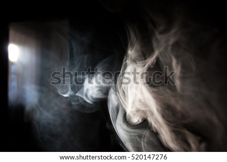 Fluffy Puffs of Smoke and Fog on Black Background and the sun's rays through the window