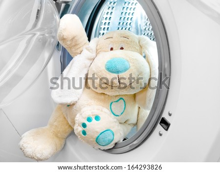 fluffy toy in the washing machine - stock photo
