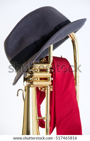 Flugelhorn Fedora - Color image of brass flugelhorn with gray fedora resting on top and draped with a red tie.