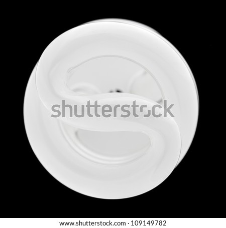 Fluorescent light bulb illuminated and taken from above and isolated against black - stock photo