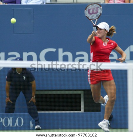 FLUSHING - AUGUST 30: Justine Henin-Hardenne of Belgium hits to Zuzana Ondraskova of the Czech Republic during the U.S. Open at Arthur Ashe Stadium on August 30, 2005 in Flushing Meadows-Corona Park. - stock photo