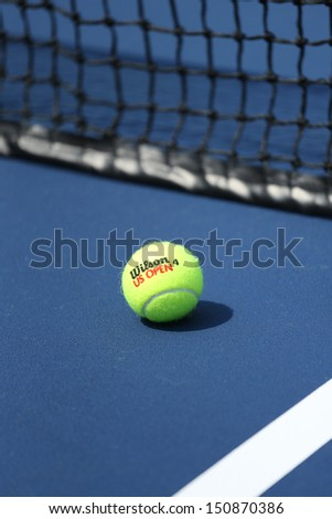 FLUSHING, NY - AUGUST 20: Wilson tennis ball on tennis court at Arthur Ashe Stadium  on August 20, 2013 in Flushing, NY. Wilson is  the Official Ball of the US Open since 1979 - stock photo