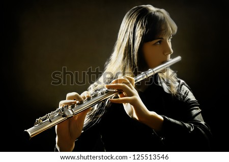Flute music flutist instruments playing. Classical orchestra musician. Focus is on the hands with instrument - stock photo
