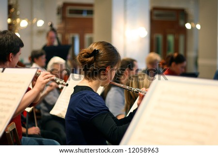 Flute player in orchestra - stock photo