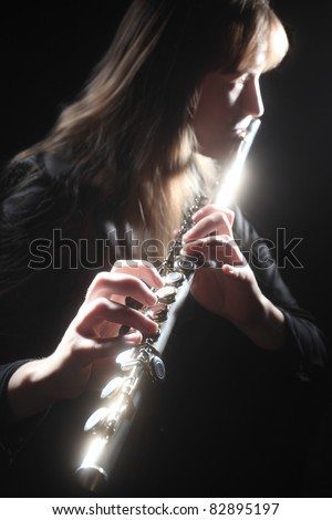 Flute playing flutist musician performer with bright musical instrument on the black background - stock photo