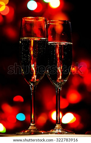 Flutes of champagne on christmas tree bokeh background - stock photo