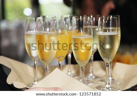 Flutes of chilled white champagne or sparkling wine being carried on a tray at a catered event or celebration