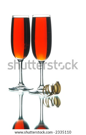 Flutes of red wine and a curl of ribbon reflecting on the table