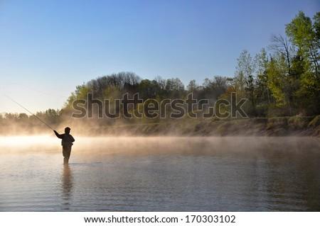 Fly fisherman fishing for Striped Bass in Nova Scotia. - stock photo