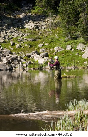 Fly fisherman fishing for trout in a mountain lake (vertical) - stock photo