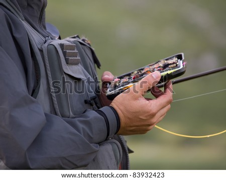 Fly fisherman is picking out the bait - stock photo