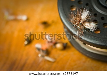 Fly fishing flies on a fly reel and antique wood. - stock photo