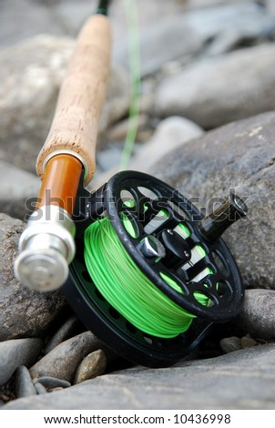 Fly fishing rod on river rocks with shallow depth of field. - stock photo
