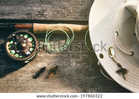 Fly fishing rod with canvas hat on wood - stock photo