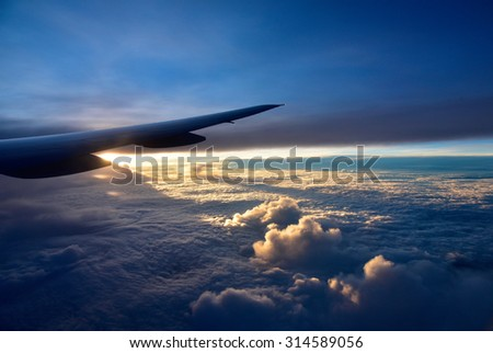 Fly from Singapore to Houston.View on the right wing passenger aircraft.Below the thick clouds illuminated by the sun.Horizontal view