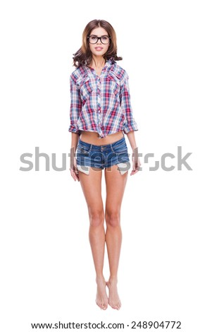 Fly like a bird! Full length of attractive young woman in glasses and funky wear jumping and looking at camera against white background - stock photo