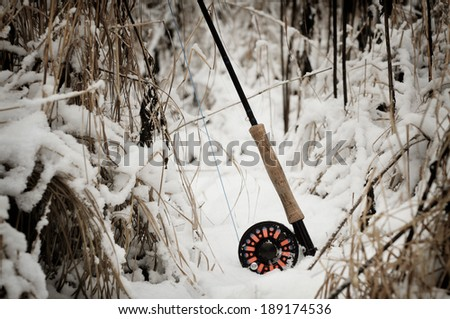 Fly rod and reel on snowy river bank - stock photo