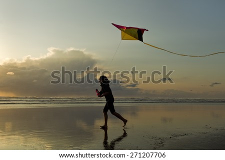 Flying a kite at sunset on the beach in Newport, Oregon. - stock photo