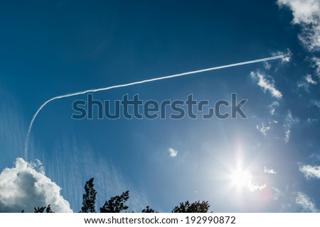 Flying airplane on the blue sky with clouds - stock photo