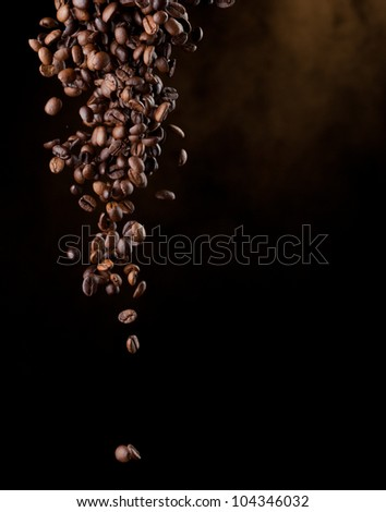 Flying coffee beans over dark - stock photo