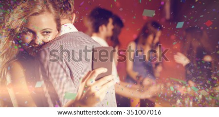 Flying colours against cute couple slow dancing together - stock photo