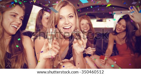 Flying colours against happy friends drinking champagne in limousine - stock photo