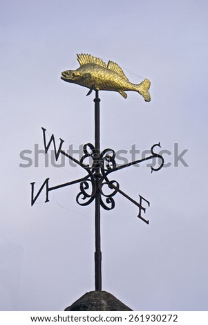 Flying Fish weathervane; gold 'flying fish' weather vane against clear blue sky  - stock photo