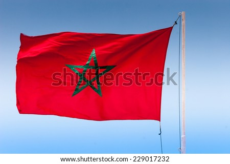 Flying Flag of Morocco against blue sky - stock photo