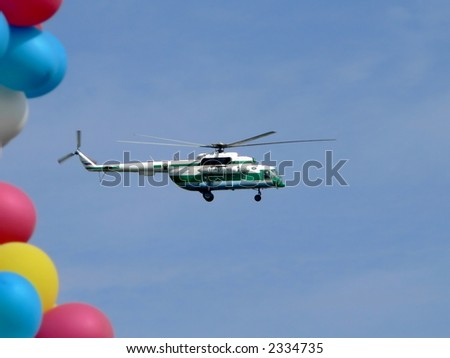 Flying helicopter and balloons on blue sky background