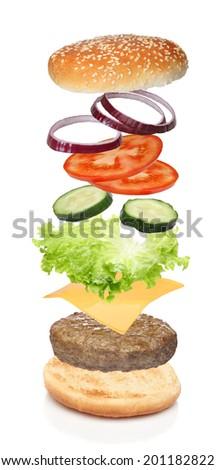 Flying ingredients of hamburger isolated on white - stock photo