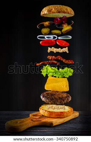 Flying ingredients of hamburger, tasty beef, bacon, salat and other vegetables.