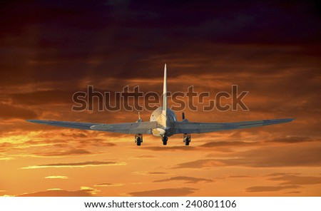 Flying old airplane with sunset background.