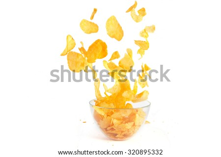 Flying over a bowl of potato crisps isolate on white background - stock photo