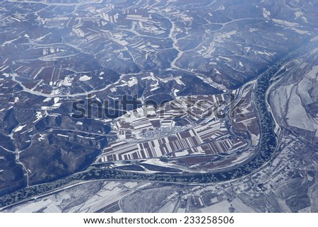 Flying over winter farmland in China - stock photo