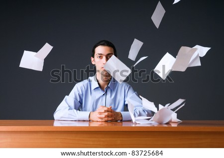Flying paper and businessman in office - stock photo