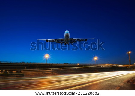 flying passenger jet plane above traffic light on express ways use as transportation background - stock photo