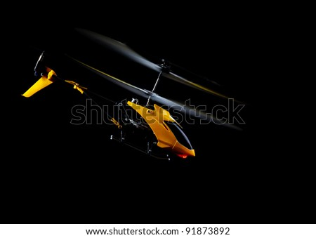 Flying RC helicopter on black - stock photo