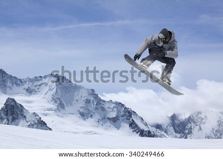 flying snowboarder on mountains. Extreme winter sport - stock photo