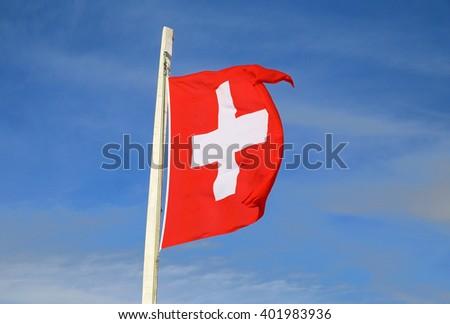 flying Swiss national flag against blue sky - stock photo