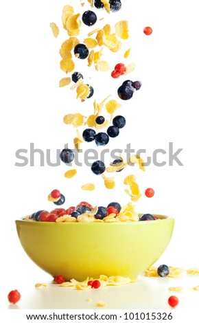 Flying to the bowl corn flakes with berries isolate on white - stock photo