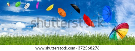 flying umbrellas in front of blue sky and green natural grass